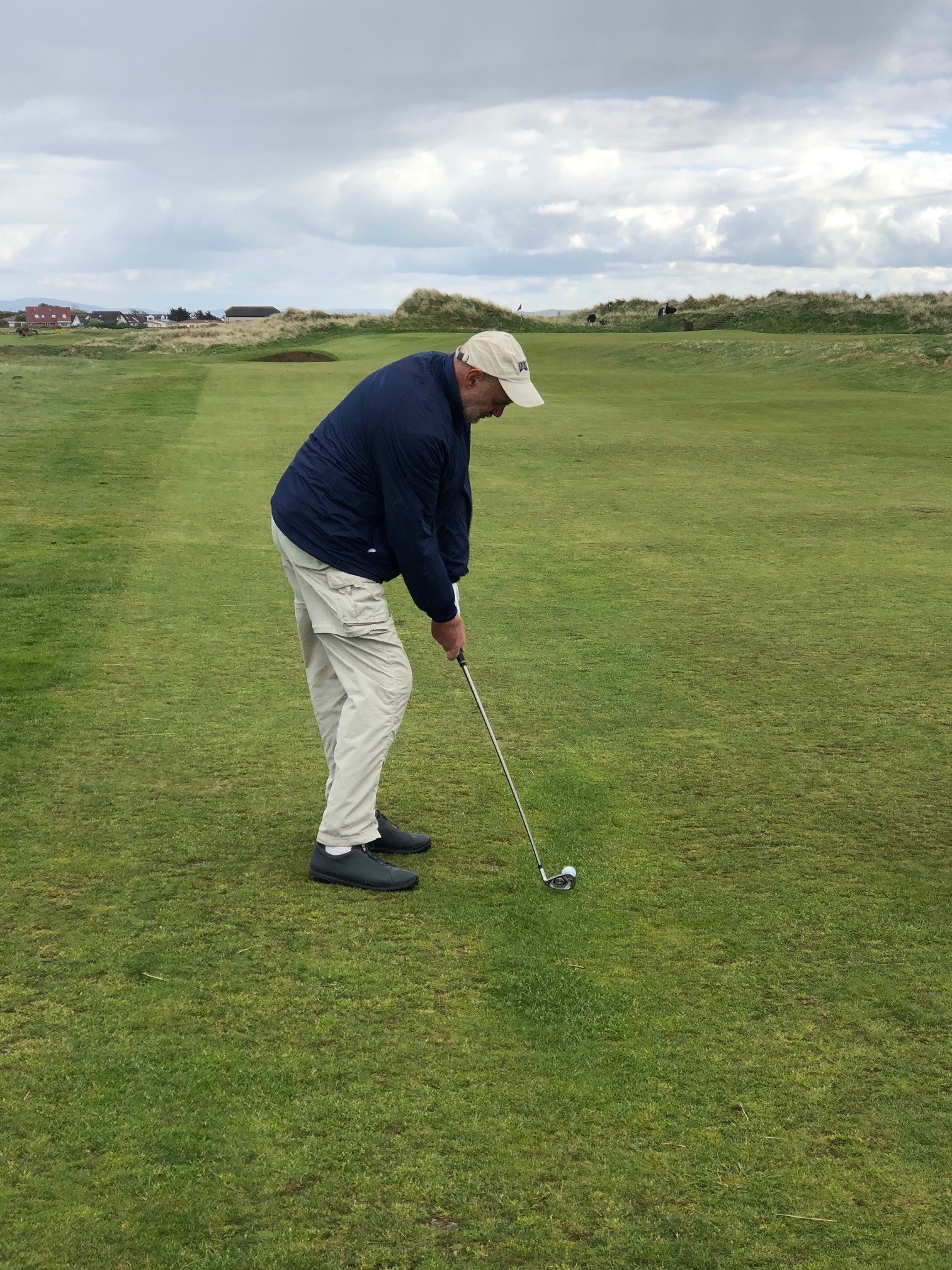 John R preparing to hit golf ball on fairway in Scotland